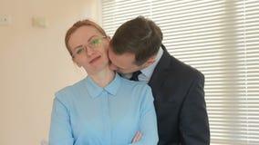 Dois empresários homem e mulher estão estando e estão sorrindo, olhando a câmera com indicação no escritório no fundo de vídeos de arquivo