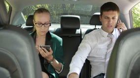 Dois empresários no assento traseiro do carro usando telefones video estoque