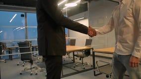 Dois empresários que agitam as mãos internas no escritório moderno Aframerican e colegas caucasianos vídeos de arquivo