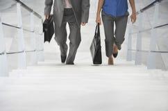 Dois empresários que andam acima das escadas Fotografia de Stock Royalty Free