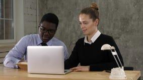 Dois empresários que sentam junto o trabalho em uma mesa de escritório que põe notas ao caderno imagem de stock royalty free