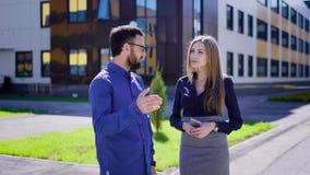 Dois empresários que sorriem e que falam Homem e executivos alegres fêmeas que comunicam-se e que sorriem no escritório filme