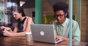 Dois empresários que trabalham em dispositivos de Digitas na cafetaria video estoque