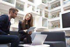 Dois empresários que usam o portátil na entrada do escritório moderno fotografia de stock royalty free