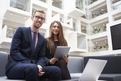 Dois empresários que usam o portátil na entrada do escritório moderno fotos de stock