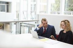 Dois empresários que usam o portátil na mesa no escritório moderno fotografia de stock royalty free