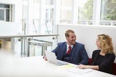 Dois empresários que usam o portátil na mesa no escritório moderno imagens de stock