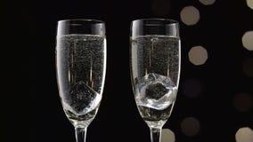 Dois encheram vidros do champanhe com um cubo de gelo em cada um Bokeh que pisca o fundo preto Fim acima video estoque