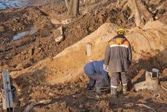 Dois equipam os trabalhadores do construtor que escavam no solo no poço da construção foto de stock