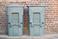 Dois escaninhos de lixo verdes velhos ao lado de uma parede de tijolo Fotografia de Stock Royalty Free