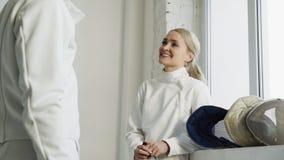 Dois esgrimistas de sorriso novos homem e mulher que compartilham da experiência durante a ruptura de cercar o fósforo dentro fotos de stock