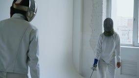Dois esgrimistas que têm o ataque do treinamento exercitam no cerco no estúdio
