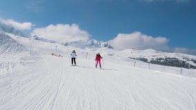 Dois esquiadores da mulher que esquiam abaixo da inclinação ideal da montanha no inverno video estoque