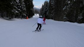 Dois esquiadores das mulheres dos esportes que esquiam nas montanhas em Forest Downhill vídeos de arquivo