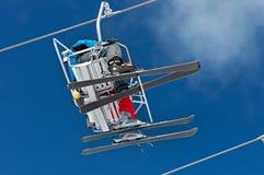 Dois esquiadores levantam à elevação de Ski Resort nas montanhas da neve do inverno no teleférico da cadeira fotografia de stock