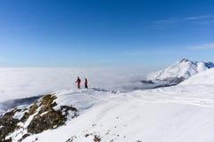 Dois esquiadores sobre a montanha acima das nuvens Fotos de Stock