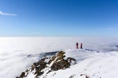 Dois esquiadores sobre a montanha acima das nuvens Fotos de Stock Royalty Free