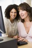 Dois estudantes adultos fêmeas que trabalham em um computador Imagem de Stock
