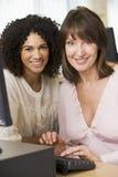 Dois estudantes adultos fêmeas que trabalham em um computador Fotos de Stock Royalty Free