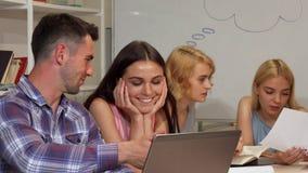 Dois estudantes alegres novos que discutem seu projeto no portátil vídeos de arquivo