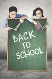 Dois estudantes atrás do texto de volta à escola Imagens de Stock Royalty Free