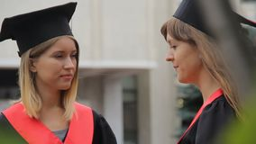 Dois estudantes bonitos que falam no parque após a cerimônia de graduação, futuro feliz filme