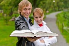 Dois estudantes com livro aberto Fotografia de Stock Royalty Free