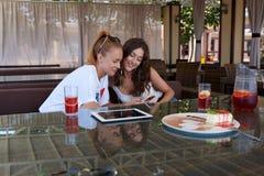 Dois estudantes de mulheres lindos que leem junto a mensagem de texto no telefone celular ao se sentar na cafetaria, Foto de Stock