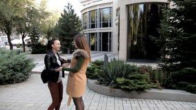 Dois estudantes encontraram-se na cidade perto da construção moderna Duas meninas cumprimentam-se: aperto e beijo vídeos de arquivo