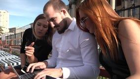 Dois estudantes fêmeas e um estudante masculino para comunicar-se em um banco no tempo ensolarado usando um portátil e um smartph filme