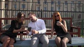 Dois estudantes fêmeas e um estudante masculino para sentar-se em um banco no tempo ensolarado usando smartphones vídeos de arquivo