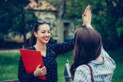 Dois estudantes fêmeas felizes estão dando altamente, comemorando o sucesso para exames aprovados em um parque imagem de stock