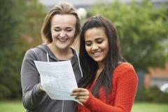 Dois estudantes fêmeas que comemoram o exame resultam junto foto de stock