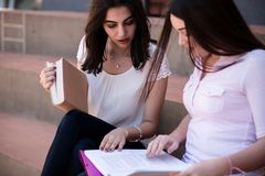 Dois estudantes fêmeas que estudam a preparação para exames junto fora Foto de Stock
