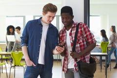 Dois estudantes masculinos que olham o telefone celular na sala de aula imagens de stock royalty free