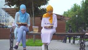 Dois estudantes muçulmanos em scarves tradicionais com os livros em suas mãos estão lendo o assento em um banco vídeos de arquivo