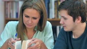 Dois estudantes novos que leem um livro na biblioteca fotografia de stock