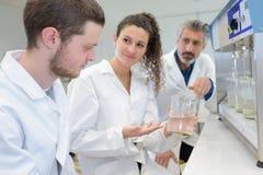 Dois estudantes novos que trabalham na ciência projetam-se no laboratório imagens de stock