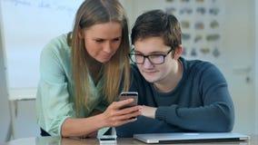Dois estudantes novos que usam o telefone durante a classe Imagens de Stock