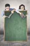Dois estudantes pequenos atrás de um quadro Foto de Stock