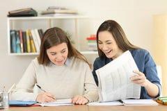 Dois estudantes que comparam notícias do jornal fotos de stock royalty free