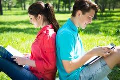 Dois estudantes que estudam no parque Fotografia de Stock Royalty Free