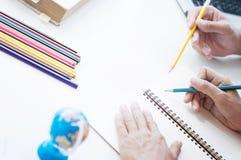 Dois estudantes que fazem trabalhos de casa junto e que ajudam-se que senta-se em uma tabela na sala de classe fotos de stock