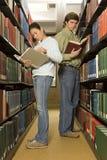Dois estudantes que leem na biblioteca imagem de stock