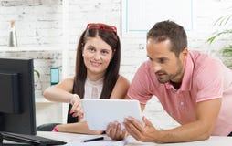 Dois estudantes que olham uma tabuleta Fotografia de Stock Royalty Free