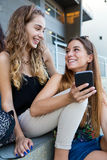 Dois estudantes que têm o divertimento com os smartphones após a classe Foto de Stock Royalty Free