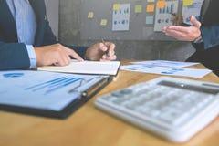Dois executivos empresariais que analisam o papel dos dados na sala de reunião fotografia de stock