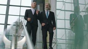 Dois executivos empresariais que conversam ao descer escadas na empresa video estoque