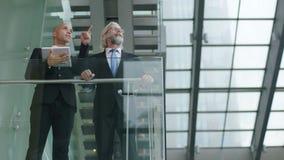 Dois executivos empresariais que discutem o negócio usando a tabuleta digital filme
