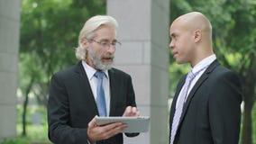 Dois executivos empresariais que discutem o negócio usando a tabuleta digital video estoque